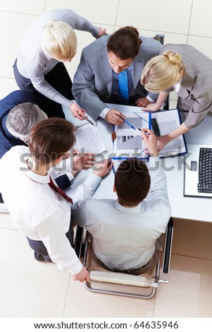 Above view of business partners sharing their ideas at meeting - stock photo