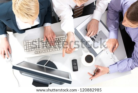 Above view of business people discussing computer work - stock photo