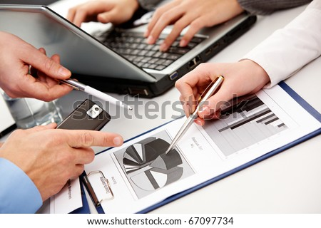 Above view of business people hands working with documents at briefing - stock photo
