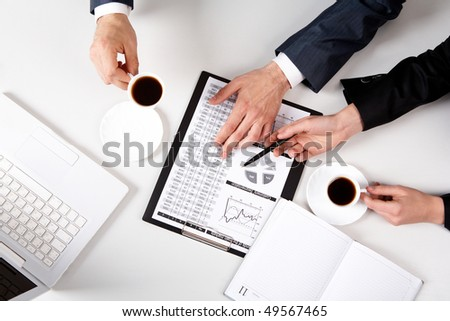 Above view of business people hands working with documents at workplace