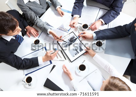 Above view of business team discussing papers - stock photo