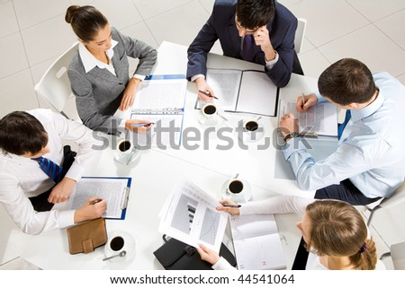 Above view of business team sitting around table and working with papers - stock photo