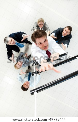 Above view of businessman ascending the ladder with his crew beneath - stock photo