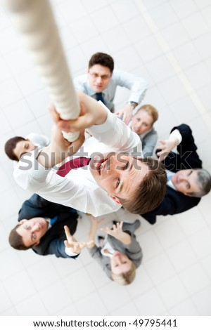 Above view of businessman ascending up the rope with his crew beneath - stock photo