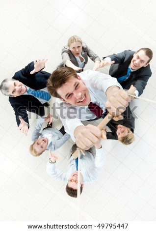 Above view of businessman holding plank on ropes and hanging on it with supporting crew beneath - stock photo