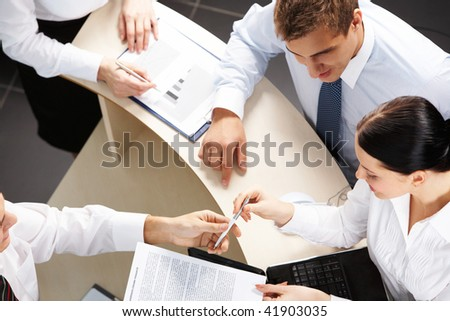 Above view of businessman passing over paper to his partner after negotiations