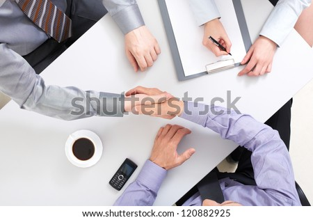 Above view of businessmen doing agreement at workplace - stock photo