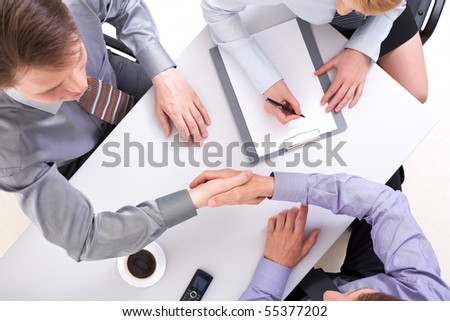 Above view of businessmen doing agreement with woman near by - stock photo