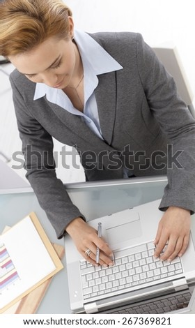 Above view of businesswoman working on laptop, sitting at desk in office, typing on keyboard. - stock photo