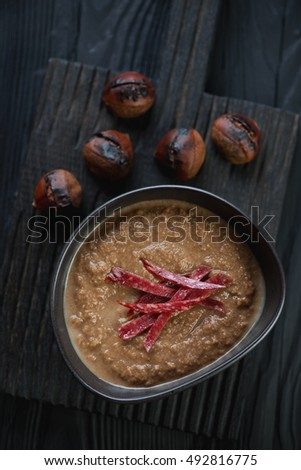 Above view of chestnut cream-soup on a dark wooden serving board