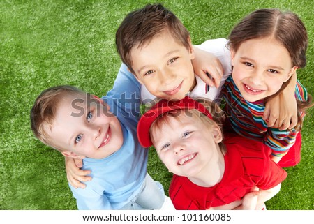 Above view of cute children hugging and smiling at cam - stock photo