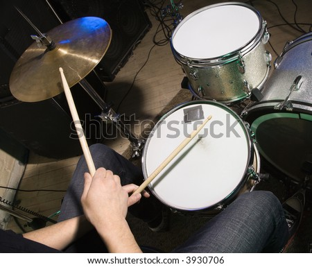 Above view of drummer's hands holding drumsticks playing on drumset. - stock photo