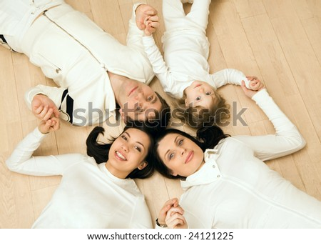 Above view of family members lying on the floor and holding each other by hands - stock photo