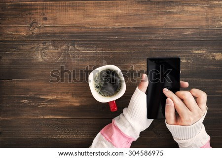 Above view of female hand holding smart phone with hot cup of coffee on wood table. Photo in vintage color image style. - stock photo