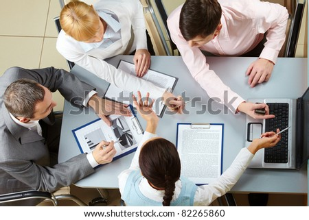 Above view of four business partners interacting at meeting - stock photo