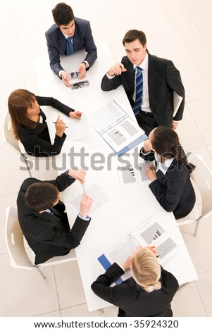 Above view of friendly team discussing documents and planning work at meeting - stock photo