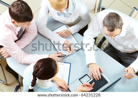 Above view of friendly workteam discussing business plan - stock photo