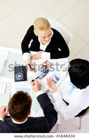 Above view of friendly workteam discussing business plan at meeting