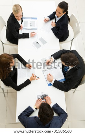 Above view of friendly workteam discussing papers at meeting - stock photo