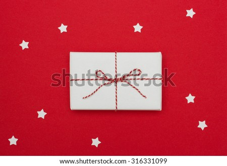 Above view of gift package on red background with white paper stars - stock photo