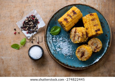 Above view of grilled sweet corn on a plate, rustic wooden background - stock photo