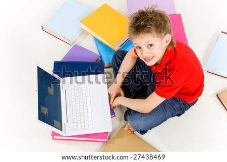 Above view of happy schoolboy sitting on floor with laptop in front - stock photo