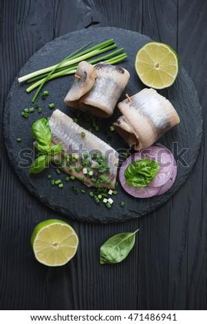 Above view of herring fillet rolls with onion, lime and basil on a black wooden background