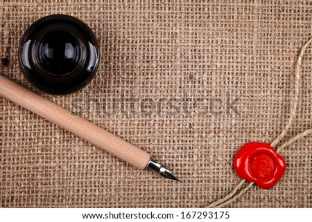 Above view of ink pot, pen and wax seal on burlap hessian  background.  - stock photo