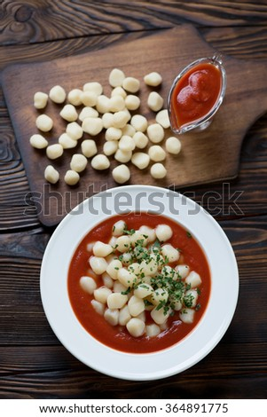 Above view of italian potato gnocchi served with tomato sauce - stock photo