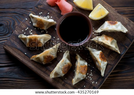 Above view of japanese gyoza dumplings on a rustic serving board