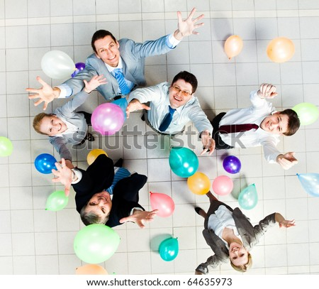Above view of joyful business people with balloons in air and on the floor