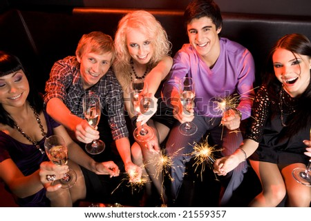 Above view of joyful friends having fun at Christmas party and looking at camera - stock photo