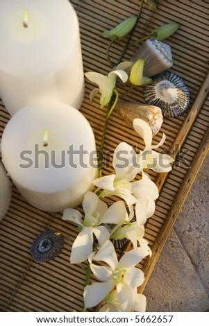 Above view of lit candles on tray with white orchid flowers.