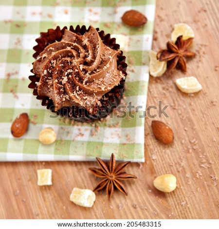 Above view of lovely fresh chocolate cupcake on green cloth. Very shallow depth of field  - stock photo