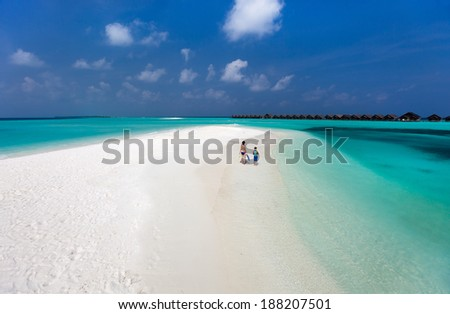 Above view of  mother and son walking along a tropical beach with snorkeling equipment - stock photo