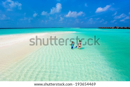 Above view of  mother and son walking at shallow turquoise ocean water with snorkeling equipment - stock photo
