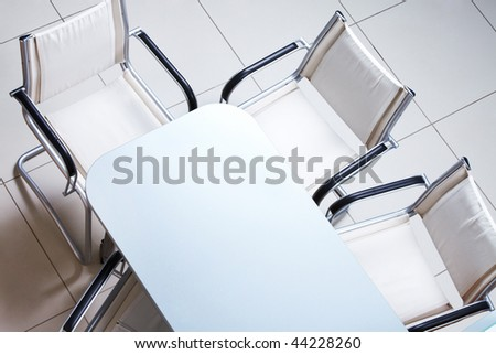 Above view of plastic table with several chairs near by - stock photo