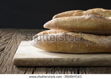 Above view of rustic loaves of bread on an old wooden table. - stock photo