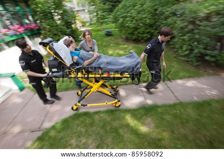 Above view of senior woman being rush to hospital by ambulance emergency medical workers - stock photo