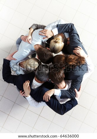 Above view of several business partners embracing each other while making circle - stock photo