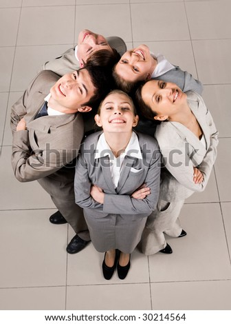 Above view of several business partners looking upwards at camera with their heads close to each other - stock photo