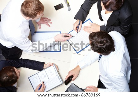 Above view of several business partners working with papers in office - stock photo