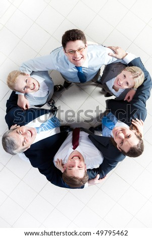 Above view of several happy business partners looking at camera while embracing each other - stock photo