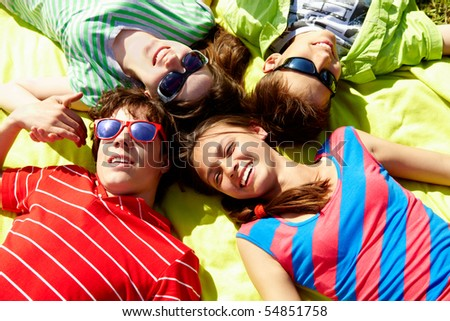 Above view of several happy teens lying head by head to each other - stock photo
