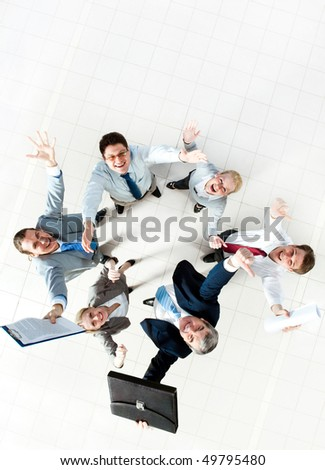 Above view of several successful partners laughing and looking at camera - stock photo