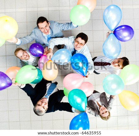Above view of several successful partners with colorful balloons looking at camera - stock photo