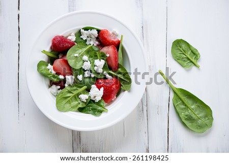 Above view of spinach, strawberry and cheese salad, studio shot - stock photo