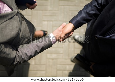 Above view of successful business partners handshaking after striking deal