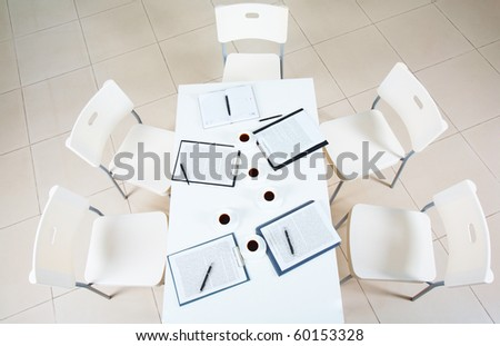 Above view of table with papers and cups of coffee surrounded by several chairs - stock photo