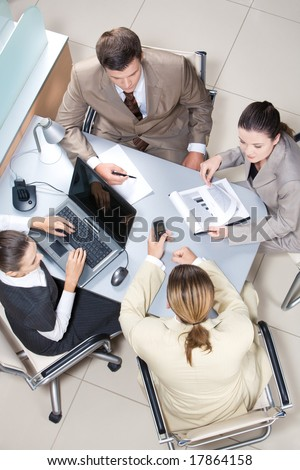 Above view of working business group sitting at table during corporate meeting - stock photo